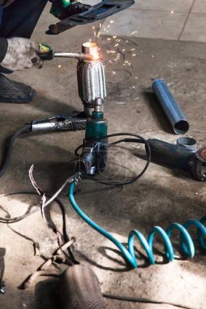 Photo pour Réparation du silencieux à ondulation du système d'échappement dans l'atelier automobile - le mécanicien fixe le tuyau sur le silencieux à ondulation par soudage à l'argon - image libre de droit