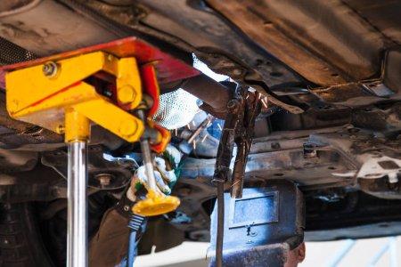 Photo pour Réparation du silencieux à ondulation du système d'échappement dans l'atelier automobile - le soudeur fixe le silencieux sur le tuyau d'échappement par soudage à l'argon - image libre de droit
