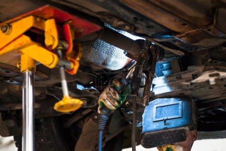 Photo pour Réparation du silencieux à ondulation du système d'échappement dans l'atelier automobile - le soudeur répare le silencieux sur le tuyau d'échappement par soudage à l'argon - image libre de droit