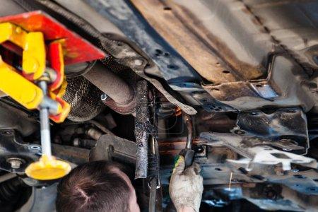 Photo pour Réparation du silencieux à ondulation du système d'échappement dans l'atelier automobile - le réparateur soude le silencieux sur la voiture par soudage à l'argon - image libre de droit