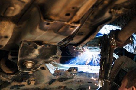 Photo pour Réparation du silencieux à ondulation du système d'échappement dans l'atelier automobile - soudeur soude le silencieux sur la voiture par soudage à l'argon - image libre de droit