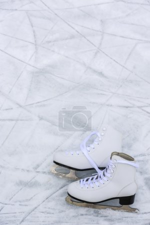 I love ice skating. Ice skates on rink background....
