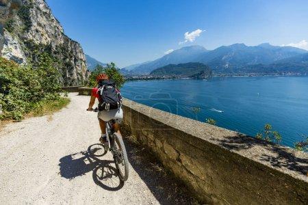 Mountain biking at sunrise woman over Lake Garda on path Sentier
