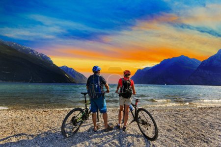 Mountain biking, couple with bikes at sunset on Lake Garda, Riva