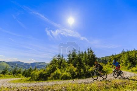 Photo for Mountain biking women and man riding on bikes in early spring mountains forest landscape. Couple cycling outdoor sport activity. - Royalty Free Image