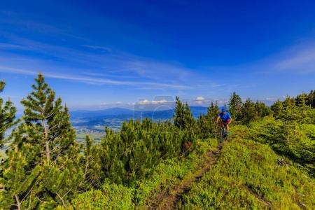 Mountain biker riding on bike in summer mountains forest landsca