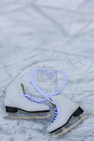 I love ice skating. Ice skates on rink background ...