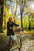 Happy active teenager riding bike in fall autumn park. Young gir