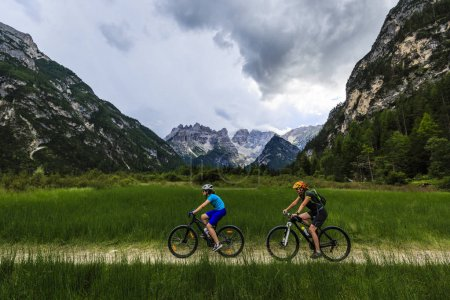 Mountain biking woman and young girl along river in Dolomites, I