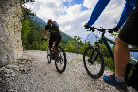 Mountain biking couple with bikes on track, Cortina d'Ampezzo, D