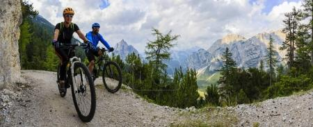 Tourist cycling in Cortina d'Ampezzo, stunning rocky mountains o