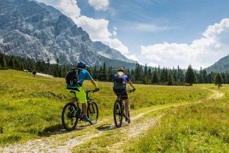 Mountain biking couple with bikes on track, Cortina d'Ampezzo, D