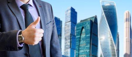 Photo pour Portrait d'un jeune homme d'affaires montrant un geste sur un paysage urbain et un fond de ciel bleu. - image libre de droit
