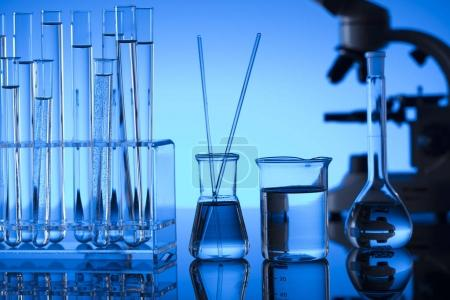 Science laboratory. Laboratory glassware, microscope, test tubes. Research and development. Blue background.