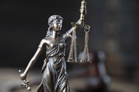 Photo pour Concept de justice. Statue de Themis et marteau du juge sur la table rustique en bois et le fond sombre. - image libre de droit