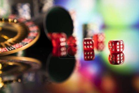 Photo pour Jeu à thème. Couper en dés, jetons poker et roue sur fond de couleur bokeh de roulette. - image libre de droit