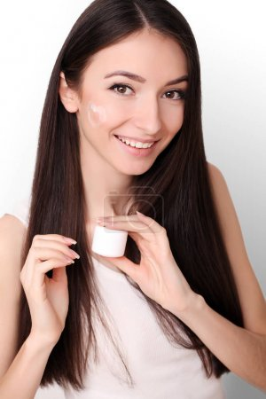 Beautiful young woman applying face cream to her cheek bone in a