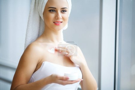 Young woman standing in bathroom and applying face cream in the