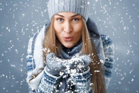 Photo pour Fille de Noël. Une fille en vêtements d'hiver soufflant sur la neige . - image libre de droit