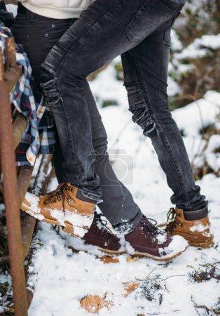 Photo pour Jambes de la jeune fille se tiennent en face des jambes du jeune homme, les amoureux heureux. Fond de neige. Chaussures de mode et jeans gris foncé - image libre de droit