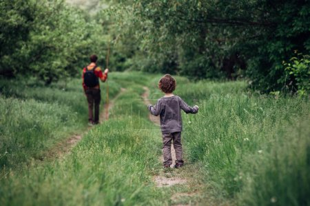 Photo for Father and son walking in spring forest - Royalty Free Image
