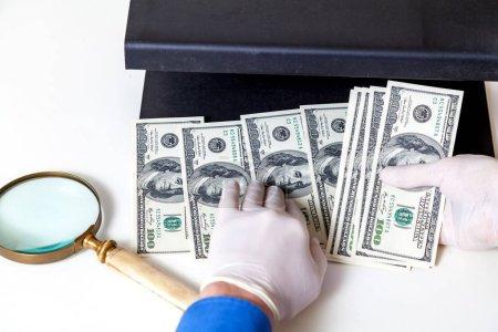 Hands in gloves check dollar bills on detector