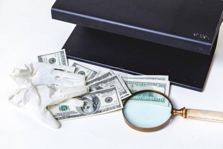 Photo pour Le chèque de change est terminé. gants de caoutchouc reposent sur des billets d'un dollar. Près d'une grande loupe et d'un détecteur de métaux - image libre de droit