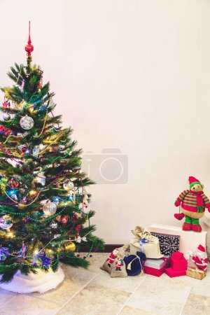 Christmas tree and gifts stand on white wall background