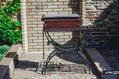 Elegant forged brazier stands in yard on summer day