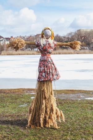 Photo pour Vacances slaves de la fin de l'hiver. Une grande poupée Shrovetide en paille dans la robe et l'écharpe d'une femme se tient sur la rive de la rivière - image libre de droit