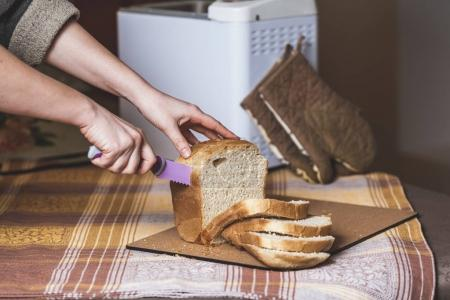 woman hands slice fresh bread slices with knife