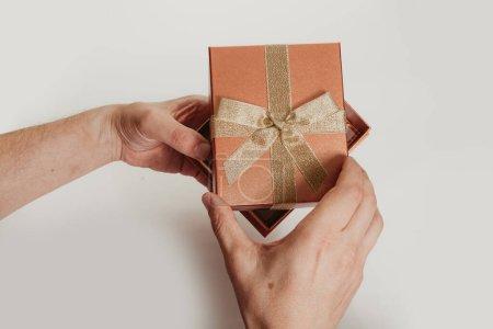 Photo pour Les mains comprennent la couverture d'une belle boîte pour un cadeau avec un arc d'un ruban d'or sur un fond blanc close-u - image libre de droit