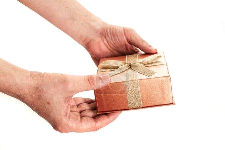 Photo pour Mains tenant une magnifique boîte-cadeau avec un arc d'un ruban or sur fond blanc close-u - image libre de droit