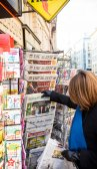 Woman purchases a Suddeutsche Zeitung german newspaper from a ne