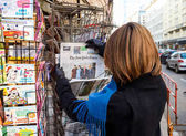 Woman purchases a New York Times with Obama and Trump newspaper