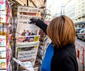 Woman purchases a Die Welt with Obama and Trump  newspaper from
