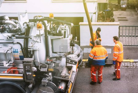 workers using sewerage truck and large pipe working on the clogg