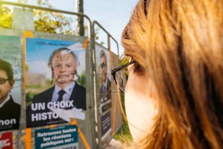 Photo pour STRASBOURG, FRANCE - 12 avril 2017 : Point de vue d'une femme regardant les affiches officielles de campagne de François Asselineau, chef de parti politique l'un des onze candidats à l'élection présidentielle française de 2017 - image libre de droit