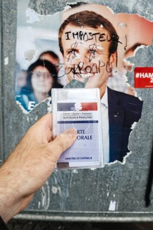 French voter registration card held in front of Emmanuel Macron