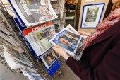 Woman buying international press with Emmanuel Macron and Marine