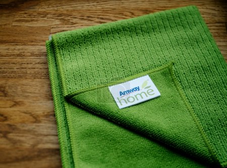 Green Microfibre cloth AMWAY HOME on wooden background