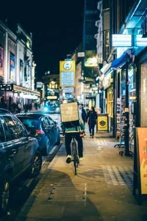 Night food delivery by Deliveroo biker in busy city