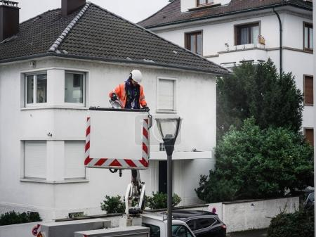 PARIS, FRANCE - December 16, 2017:  Worker cleaning repairing changing the light tube of a light mast in Paris for the night security and safety in the neighborhood