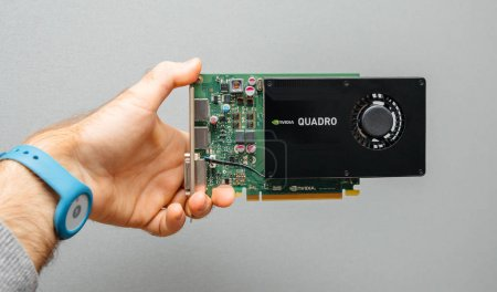 PARIS, FRANCE - December 6, 2017: Man hand holding against gray background powerful NVIDIA GPU video card from the Quadro line used in professional video production in bitcoin cryptocurrency mining