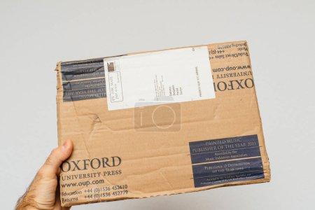 PARIS, FRANCE - December 18, 2017: Man holding Oxford Library Press cardboard parcel against white background