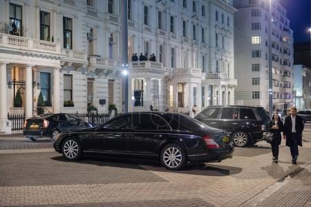 LONDON, UNITED KINGDOM - March 9 2017: British pedestrians walking next to Mercedes-Maybach luxury limousine parked on the Exhibition Rd, Kensington London.