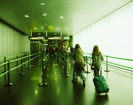 BARCELONA, SPAIN - December 18, 2017: Defocused blur silhouettes of people walking with luggage trolleys in the Barcelona Airport toward embarking gates and passport control