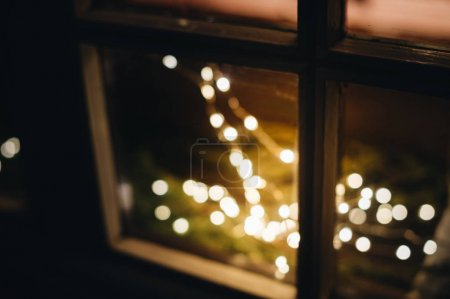 Light decorations during Christmas holiday season on windows - defocused view of lights with bokeh