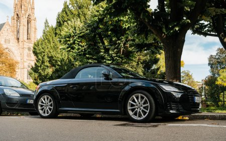 STRASBOURG, FRANCE - OCT 1, 2017: Luxury Audi TT sport car parked in city with church building in the background