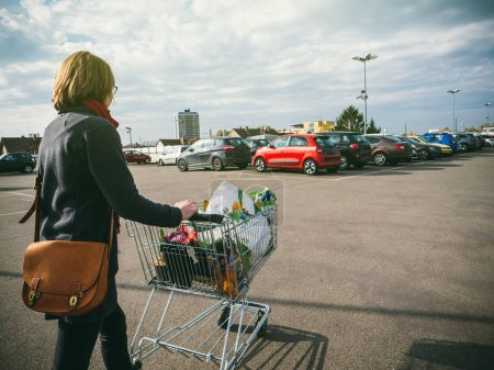 Woman pushing supermarket cart full with food and household products tot he car parked on the roof parking